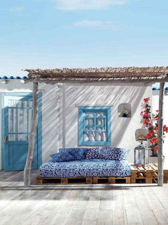 Mediterranean style sitting area in blues and whites with plush pillows, lanterns and colorful plants